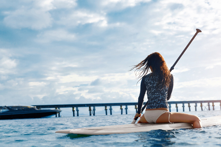 Travel Adventure. Beautiful Fit Woman Paddling On ( SUP, Surfing ) Board In Sea At Resort. Recreation, Water Sports. Summer Fun, Holidays Vacation. Healthy Active Lifestyle. Leisure Activity. Wellness