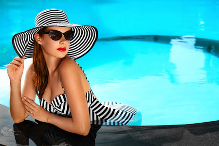 Photo pour Summer Holidays. Travel Vacation To Spa Resort. Beautiful Fashionable Healthy Young Woman With Sexy Body In Bikini, Sunglasses, Sun Hat At Swimming Pool. Healthy Lifestyle. Beauty, Wellness Concept - image libre de droit
