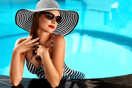 Summer Woman Beauty, Fashion. Beautiful Healthy Woman With Sexy Body In Elegant Bikini, Sun Hat, Sunglasses Relaxing In Swimming Pool On Holidays Travel Vacation To Spa Resort. Summertime Relaxation