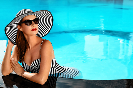 Photo pour Summer Woman Beauty, Fashion. Beautiful Healthy Woman With Sexy Body In Elegant Bikini, Sun Hat, Sunglasses Relaxing In Swimming Pool On Holidays Travel Vacation To Spa Resort. Summertime Relaxation - image libre de droit