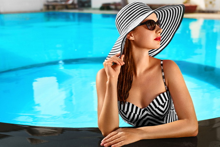 Foto per Summer Holidays. Travel Vacation To Spa Resort. Beautiful Fashionable Healthy Young Woman With Sexy Body In Bikini, Sunglasses, Sun Hat At Swimming Pool. Healthy Lifestyle. Beauty, Wellness Concept - Immagine Royalty Free