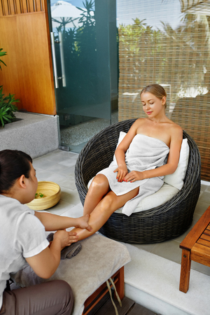 Spa Foot Therapy. Woman Body Care Treatment. Masseur Massaging Young Female Feet With Aromatherapy Oil Outside In Spa Salon Garden. Relaxing Recreational Massage. Skin Care, Beauty Procedure Concept