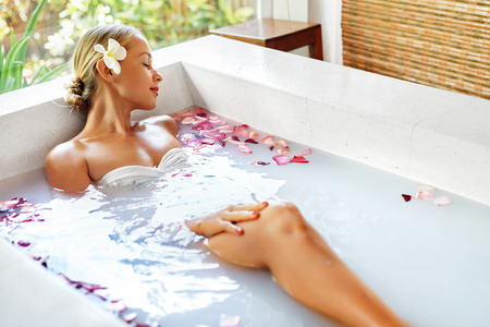 Photo pour Spa Relaxation. Woman Body Care. Beautiful Sexy Caucasian Blonde Girl In Bikini Lying In Flower Bath In Resort Day Spa Salon. Beauty Treatment, Skin Care Therapy. Wellness. Healthy Lifestyle Concept - image libre de droit