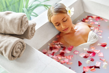 Spa Relax In Flower Bath. Woman Health And Beauty. Closeup Beautiful Sexy Girl Bathing With Rose Petals In Renew Day Spa Salon. Beauty Treatment, Aromatherapy Skin Body Care Therapy. Wellness Concept