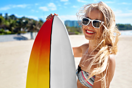 Photo pour Summer Travel Beach Vacation. Close Up Of Healthy Happy Beautiful Sexy Woman In Sunglasses With Surfboard Having Fun By Sea. Active Lifestyle. Leisure Sporting Activity. Water Sports. Summertime Relax - image libre de droit