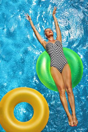 Foto de Summer Vacations. Beautiful Sexy Smiling Woman With Perfect Fit Body, Healthy Skin In Swimwear Sunbathing, Floating On Float Swim Ring In Swimming Pool Water. Enjoyment. Beauty, Wellness. Recreation - Imagen libre de derechos