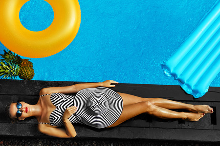 Foto de Woman Summer Fashion. Happy Sexy Smiling Girl With Fit Body, Long Legs, Healthy Skin In Bikini, Sun Hat, Sunglasses Sunbathing By Swimming Pool On Travel Holidays Vacation. Beauty, Wellness, Lifestyle - Imagen libre de derechos