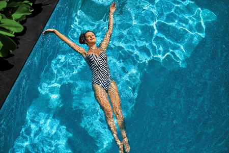 Photo pour Woman In Pool Water. Beautiful Happy Girl With Sexy Fit Body Relaxing, Floating In Swimming Pool At Spa Hotel. Summer Holidays Vacation. Healthy Lifestyle. Wellness, Beauty, Health Concept. Recreation - image libre de droit