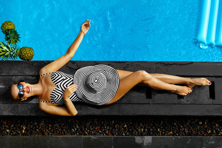 Photo for Woman Summer Fashion. Happy Sexy Smiling Girl With Fit Body, Long Legs, Healthy Skin In Bikini, Sun Hat, Sunglasses Sunbathing By Swimming Pool On Travel Holidays Vacation. Beauty, Wellness, Lifestyle - Royalty Free Image