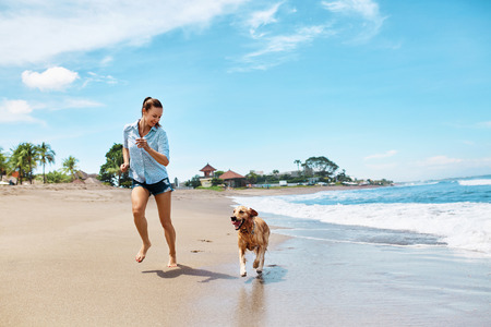 Photo pour Summer Fun On Beach. Beautiful Happy Woman Running With Her Dog, Golden Retriever, Pet On Wet Sand In Sea Water. Holidays Vacations At Tropical Resort. Summertime Travel Concept. - image libre de droit