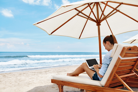 Foto de Work At Beach. Successful Freelancer Business Woman Working Online In Internet On Laptop Computer, Typing On Keyboard Relaxing By Sea. Freelance Outdoors Work. People Communication, Technology Concept - Imagen libre de derechos