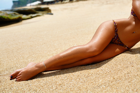 Photo for Woman Legs On Beach. Beautiful Sexy Girl With Slim Fit Body, Healthy Smooth Silky Sun Tanned Skin And Long Depilated Legs Relaxing On Sand. Female In Bikini Sunbathing In Summer. Human Body Part - Royalty Free Image