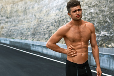 Stomach Ache. Closeup Portrait Of Athletic Man With Fit Muscular Body Touching Belly, Suffering From Abdominal Pain. Handsome Fitness Runner Feeling Bad After Running Outdoors. Sport Injury Concept