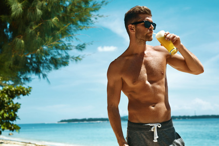 Photo pour Healthy Drink. Handsome Fitness Male Model Having Fun, Enjoying Travel Vacation. Portrait Of Athletic Sexy Man With Muscular Body Drinking Refreshing Juice Cocktail On Tropical Sea Beach. Summertime - image libre de droit