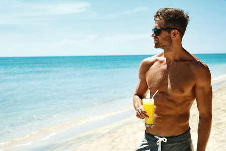 Summer Relax. Portrait Of Athletic Sexy Man With Muscular Body Drinking Fresh Juice Smoothie Cocktail On Tropical Beach. Handsome Fitness Male Model Sunbathing, Enjoying Refreshing Drink On Vacation