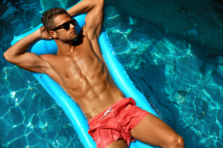 Photo pour Man Summer Fashion. Beautiful Male With Sexy Body In Swimwear, Fashionable Sunglasses Tanning, Floating In Swimming Pool Water At Relax Spa Resort. Fitness Model With Skin Sun Tan Relaxing On Vacation - image libre de droit