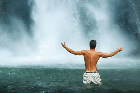 Freedom Man. Free Happy Healthy Male Relaxing In Pure Water Near Beautiful Paradise Waterfall With Hands Up, Enjoying Rain Forest Nature Beauty On Travel Vacation. Enjoyment, Health, Wellness Concept