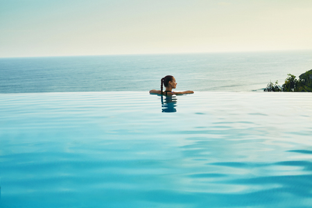 Photo for Luxury Resort. Woman Relaxing In Infinity Swimming Pool Water. Beautiful Happy Healthy Female Model Enjoying Summer Travel Vacation, Looking At Sea View. Summertime Recreation, Relax And Spa Concept. - Royalty Free Image