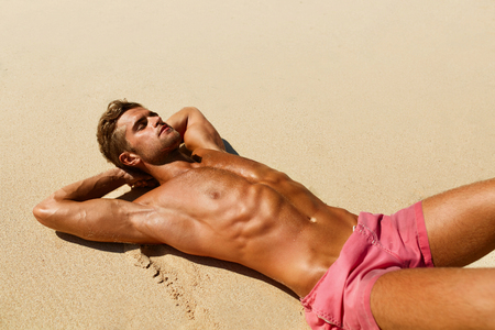 Photo pour Man Body On Beach In Summer. Handsome Sexy Fit Male With Healthy Skin Sun Tan Tanning At Luxury Relax Spa Resort. Beautiful Fitness Model Relaxing, Sunbathing Lying On Sand. Summertime Travel Vacation - image libre de droit