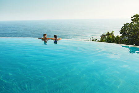 Photo for Romantic Vacation For Couple In Love. Happy People Relaxing In Infinity Edge Swimming Pool Water, Enjoying Beautiful Sea View. Man, Woman Together On Summer Travel To Luxury Resort. Summertime Relax - Royalty Free Image