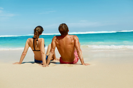 Couple On Beach In Summer. Romantic People In Love Relaxing On Sand, Enjoying Sea View. Happy Man, Beautiful Woman On Honeymoon Summer Travel Vacation At Luxury Resort. Relationships, Summertime Relax
