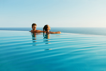 Photo for Couple In Love At Luxury Resort On Romantic Summer Vacation. People Relaxing Together In Edge Swimming Pool Water, Enjoying Beautiful Sea View. Happy Lovers On Honeymoon Travel. Relationship, Romance - Royalty Free Image