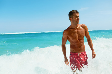 Sexy Man On Beach In Summer. Handsome Male With Fit Body, Healthy Skin Sun Tan Coming Out Of Sea At Luxury Relax Spa Resort. Beautiful Happy Guy Relaxing, Enjoying Holidays Travel Vacation. Summertime