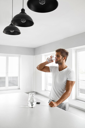 Drinking Water. Handsome Young Man With Sexy Fit Body Drinking Fresh Water From Glass In Morning. Thirsty Fitness Male Model Enjoying Refreshing Drink Indoors. Healthy Nutrition Concept
