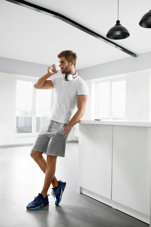 Photo pour Drinking Water. Handsome Young Man With Sexy Fit Body Drinking Fresh Water From Glass In Morning. Thirsty Fitness Male Model Enjoying Refreshing Drink Indoors. Healthy Nutrition Concept - image libre de droit