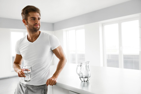 Foto de Healthy Nutrition. Handsome Young Man With Sexy Fit Body Holding A Glass Of Fresh Water In Kitchen. Athletic Smiling Fitness Male Drinking Water In Morning. Hydration, Health And Drink Concepts. - Imagen libre de derechos
