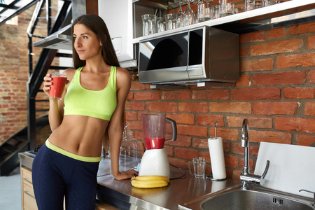 Photo for Detox Smoothie Diet Drink. Healthy Woman With Fit Body Drinking Fresh Organic Juice In Kitchen. Beautiful Happy Smiling Girl Model In Fitness Sportswear Enjoying Weight Loss Food. Nutrition Concept - Royalty Free Image