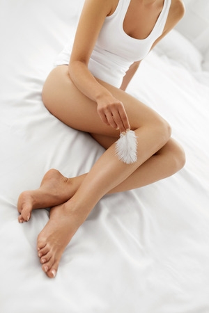 Photo pour Beautiful Soft Skin. Closeup Of Long Woman Legs With Perfect Hairless Smooth And Silky Skin, Woman's Hand Touhing Her Sexy Slender Leg With White Feather. Hair Removal, Beauty Body Care Concepts - image libre de droit