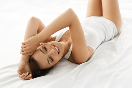 Photo for Beauty And Health. Beautiful Smiling Woman With Fresh Soft Skin And Natural Makeup In Underwear Having Fun Lying On White Bed. Healthy Happy Female Model Relaxing Indoors. Body And Skin Care Concept - Royalty Free Image