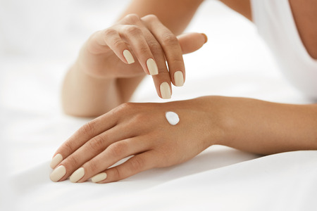 Photo pour Woman Hands With Cream. Closeup Of Beautiful Female Hands With Natural Manicure Nails Applying Cosmetic Lotion On Healthy Soft Skin, Touching Cream On Her Hand. Beauty And Body Care Concept - image libre de droit