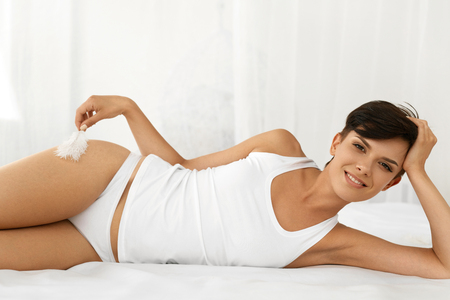 Photo pour Beauty And Health. Beautiful Smiling Woman With Fresh Soft Skin And Natural Makeup In Underwear Having Fun Lying On White Bed. Healthy Happy Female Model Relaxing Indoors. Body And Skin Care Concept - image libre de droit