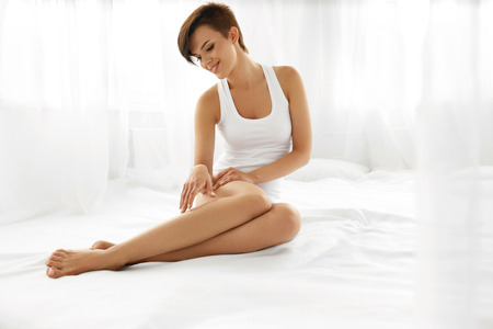 Photo for Woman Body Care. Beautiful Happy Healthy Girl Touching Sexy Long Legs. Female Enjoying Perfect Hairless Smooth Soft And Silky Skin Sitting On White Bed. Beauty, Hair Removal And Epilation Concept - Royalty Free Image