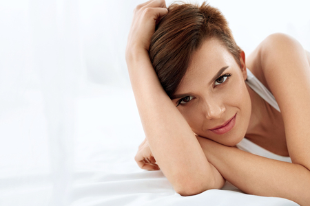 Photo pour Woman's Health. Closeup Portrait Of Beautiful Smiling Woman With Fresh Face, Soft Skin Having Fun Lying On White Bed. Healthy Happy Girl With Natural Makeup Relaxing Indoors. Beauty, Skin Care Concept - image libre de droit