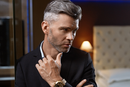 Photo pour Handsome Man In Fashion Clothes In Luxury Interior. Closeup Portrait Of Successful Wealthy Confident Business Man In Stylish Elegant Suit, Expensive Watch In Fashionable Luxurious Apartment. Wealth - image libre de droit