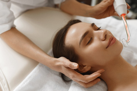 Photo for Face Beauty Treatment. Woman Getting Facial Darsonval Therapy Using High Frequency D'Arsonval, Skin Care Device For Anti Spot And Acne Treatment At Cosmetology Center. High Resolution Image - Royalty Free Image