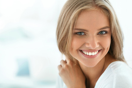 Foto de Beautiful Woman Smiling. Portrait Of Attractive Happy Healthy Girl With Perfect Smile, White Teeth, Blonde Hair And Fresh Face Smiling Indoors. Beauty And Health Concept. High Resolution Image - Imagen libre de derechos