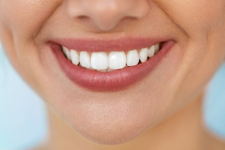 Foto de Beautiful Smile With White Teeth. Closeup Of Smiling Woman Mouth With Natural Plump Full Lips And Healthy Perfect Smile. Teeth Whitening, Dental Health And Lip Care Concepts. High Resolution Image - Imagen libre de derechos