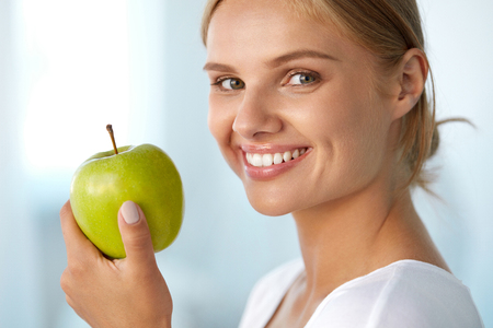 Photo pour Woman With Apple. Closeup Portrait Of Beautiful Happy Smiling Girl With White Smile, Healthy Teeth Holding Natural Organic Green Apple. Dental Health, Healthy Eating Concepts. High Resolution Image - image libre de droit
