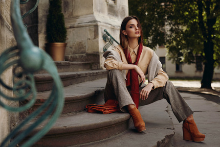 Photo for Fashion Model In Street. Beautiful Sexy Woman In Stylish Fashionable Fall Clothes: Shirt, Scarf, Pants, Sweater, Shoes Sitting On Stairs In Spring. Girl In High Fashion Autumn Clothing Posing Outdoors - Royalty Free Image