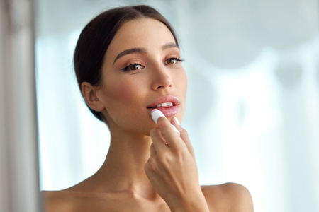 Photo pour Lips Protection. Beautiful Woman With Beauty Face, Sexy Full Lips Applying Lip Balm, Lipcare Stick On. Portrait Of Female Model With Natural Makeup. Lips Skin Care Cosmetics Concept. High Resolution - image libre de droit