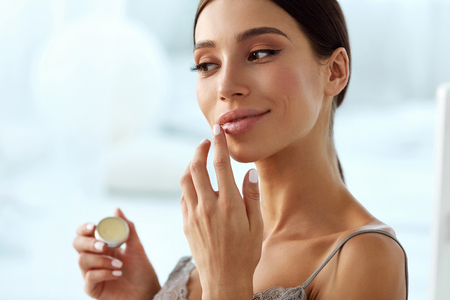 Lips Skin Care. Beautiful Woman With Beauty Face Applying Lip Balsam, Lipbalm On Full Sexy Lips. Portrait Of Smiling Female Model With Soft Skin And Natural Nude Makeup Touching Lips. High Resolution