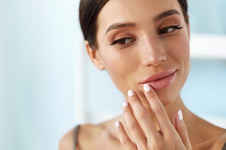 Foto de Lips Skin Care. Beautiful Woman With Beauty Face Applying Lip Balsam, Lipbalm On Full Sexy Lips. Portrait Of Smiling Female Model With Soft Skin And Natural Nude Makeup Touching Lips. High Resolution - Imagen libre de derechos