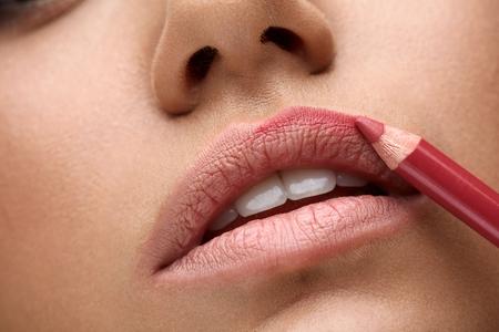 Photo pour Makeup Lips. Closeup Of Beautiful Young Woman Applies Color Contour Lip Pen, Lip Liner. Girl Contouring Sexy Full Lips With Lip Pencil, Beauty Product. Cosmetics Concept. High Resolution Image - image libre de droit