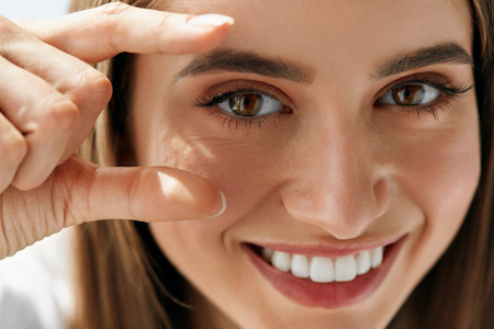 Foto de Healthy Eyevision. Beautiful Happy Woman With Focus On Her Eyes. Closeup Of Smiling Girl With Cheerful Look, Natural Makeup And Smooth Skin. Ophthalmology And Eyecare. High Resolution - Imagen libre de derechos
