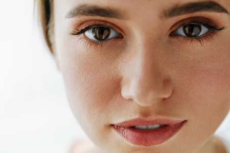 Foto de Eye Health And Care. Portrait Of Girl Face With Smooth Healthy Skin And Perfect Natural Makeup. Closeup Of Beautiful Woman With Big Brown Eyes And Eyebrows On White Background. High Resolution Image - Imagen libre de derechos