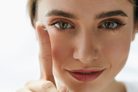 Photo pour Eye Care And Contact Lenses For Eyes. Closeup Of Beautiful Woman Face With Smooth Skin And Perfect Makeup Applying Eyelens With Finger. Female Model Putting In Contact Eye Lens. Vision And Health - image libre de droit